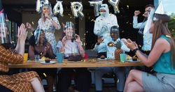 Birthday party during COVID-19. Young happy multiethnic friends dancing under confetti with safety measures slow motion.