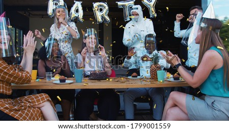 Birthday party during COVID-19. Young happy multiethnic friends dancing under confetti with safety measures slow motion. Photo stock ©