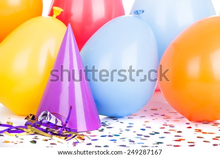 Birthday party hat and balloons with confetti and a noisemaker