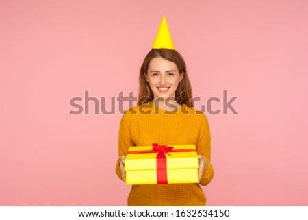 Birthday party. Portrait of happy red hair girl with party cone on head holding gift box and smiling at camera, congratulating on holidays and giving present. studio shot isolated on pink background