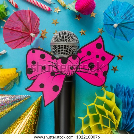 Birthday party with party hats microphone and streamers on a blue festive background with bright elements and with copy space, a concept of parties and karaoke #1022100076