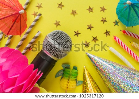 Birthday party with party hats microphone and streamers on a yellow festive background with bright elements and with a copy space, a concept of parties and karaoke #1025317120