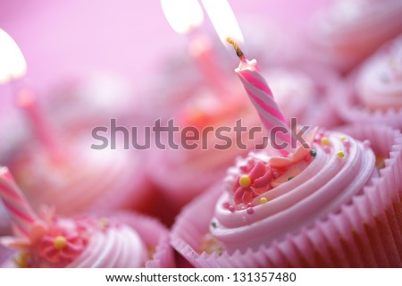 Birthday pink cupcakes with burning candles