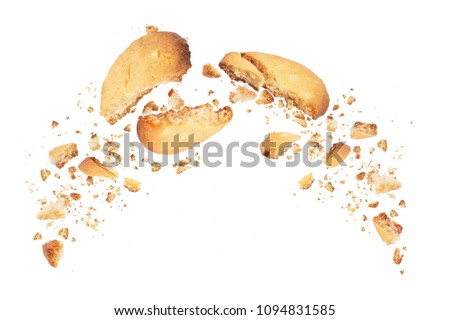 Biscuits broken into two halves with falling crumbs down, isolated on white background