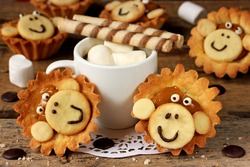 Biscuits in the form of a monkey face, coffee with marshmallows. Creative sweets to children's holiday table.