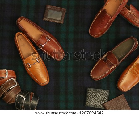 Bison leather accessories and shoes in an aerial shot against a dark background. This pictures has a holiday Christmas theme to it, as these are gift ideas and presents.