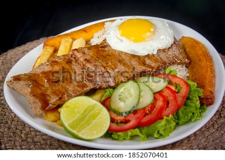 BISTECK A LO POBRE (Steak, French fries, salad, fried banana, egg and white rice) Foto stock ©