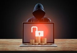 Bitcoin and cryptocurrency cybersecurity concept with hacker behind the laptop with coins.