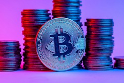 Bitcoin and stacks of coins in neon light.