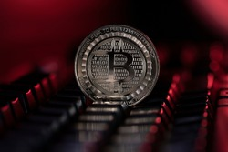 Bitcoin BTC cryptocurrency physical coin placed on the computer keyboard and lit with red light.