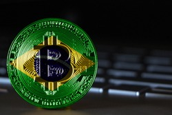 Bitcoin close-up on keyboard background, the flag of Brazil is shown on bitcoin.