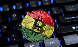 Bitcoin close-up on keyboard background, the flag of Ghana is shown on bitcoin.