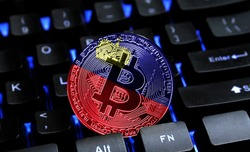 Bitcoin close-up on keyboard background, the flag of Liechtenstein is shown on bitcoin.