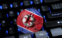Bitcoin close-up on keyboard background, the flag of North Korea is shown on bitcoin.