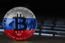 Bitcoin close-up on keyboard background, the flag of russia is shown on bitcoin.