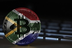 Bitcoin close-up on keyboard background, the flag of South Africa is shown on bitcoin.