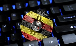 Bitcoin close-up on keyboard background, the flag of Uganda is shown on bitcoin.