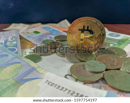 Bitcoin coin in gold dominating the old traditional currencies presented by various coins and paper money bills in different currencies