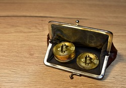 Bitcoin coin in wallet for carrying money and coins. Сryptocurrency trading exchange. BTC mining and investing concept. Blockchain and financial technology. Crypto prices and market capitalization