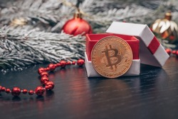 Bitcoin coin near a gift box among the branches of a Christmas tree with snow, Christmas balls, red beads on a dark background with a copy space. Beautiful new year, Christmas background with bitcoin.