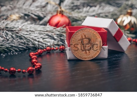 Photo of  Bitcoin coin near a gift box among the branches of a Christmas tree with snow, Christmas balls, red beads on a dark background with a copy space. Beautiful new year, Christmas background with bitcoin.
