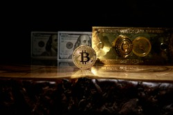 Bitcoin coin on a wooden table. Digital currency. Digital money. Bitcoin coin and banknote stand on a wooden table.