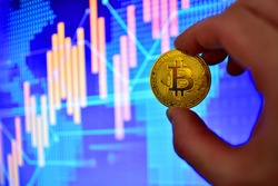Bitcoin coin on background of cryptocurrency trading exchange chart. BTC mining and investing concept. Blockchain and financial technology. Crypto prices and charts, listed by market capitalization