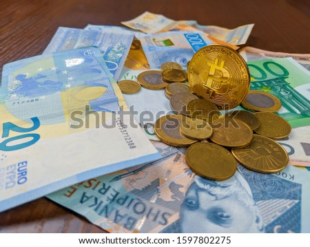 Bitcoin coin standing among various different world currencies in form of coins and paper money as a new and promising future currency