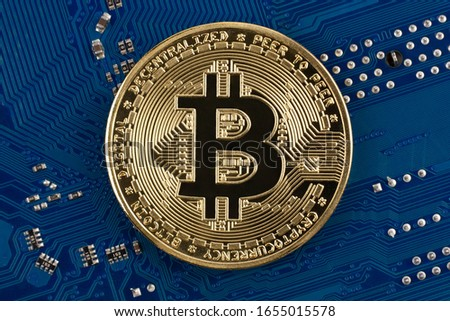 Bitcoin coin symbol face side on blue electronic circuit board background. Close-up, blue background. Business, money, cryptocurrency concept.