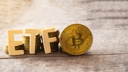 Bitcoin coin with ETF text Put on  wooden floor, Concept Entering the Digital Money Fund.