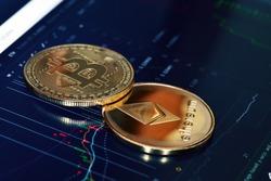 Bitcoin. Crypto currency Bitcoin, BTC, Bit Coin. Bitcoin and Ethereum golden coins on a chart. Blockchain technology, bitcoin mining concept