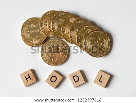 "Bitcoin crypto currency with letter tiles spelling out ""HODL"" which is insider lingo for ""hold"", overhead view. #1232397616"