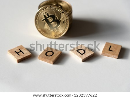 "Bitcoin crypto currency with letter tiles spelling out ""HODL"" which is insider lingo for ""hold"", angled view. #1232397622"