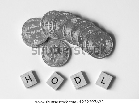 "Bitcoin crypto currency with letter tiles spelling out ""HODL"" which is insider lingo for ""hold"", overhead black and white. #1232397625"
