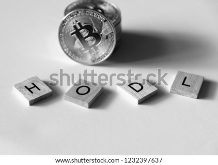 "Bitcoin crypto currency with letter tiles spelling out ""HODL"" which is insider lingo for ""hold"", low angle black and white. #1232397637"