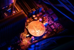 Bitcoin Cryptocurrency coin on a PC computer motherboard, crypto currency mining concept.