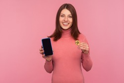 Bitcoin cryptocurrency payments. Happy excited woman with brown hair holding btc golden coin and cellphone looking at camera with toothy smile. Indoor studio shot isolated on pink background