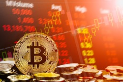 Bitcoin cryptocurrency stock trading background concept. Golden bitcoin over many international money coins with abstract trading red market data chart background.