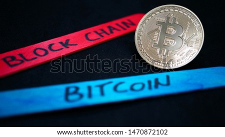 bitcoin gold coin among wooden sticks of various colors with various writings on a black background, in macro view