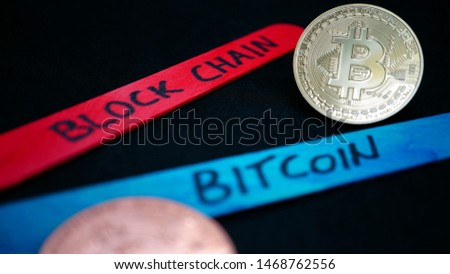 bitcoin gold coin and blurry copper bitcoin coin among wooden sticks of various colors with various writings on a black background, in macro view