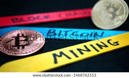 bitcoin gold coin and copper bitcoin coin among wooden sticks of various colors with various writings on a black background, in macro view