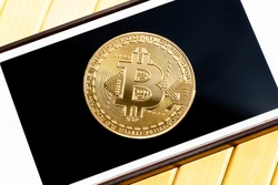 Bitcoin gold coin laying on a smartphone screen, closeup, top view. Golden coin on a mobile phone display, seen from above, app cryptocurrency day trading, virtual currency payment abstract concept