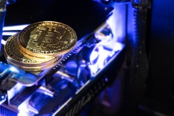 Bitcoin golden coins on a gpu with blue neon light. The future of money.