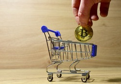 Bitcoin in shopping cart. Man's hand puts a BTC gold crypto coin in mini shopping trolley. Blockchain and financial technology. Buying goods and food in the store for cryptocurrency. Investing concept