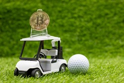 Bitcoin is on golf cart with golf ball are on green grass