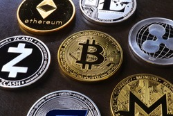 Bitcoin, litecoin and ripple coins currency .Virtual money represented by real coins placed against a dark background. Golden bitcoin in the middle.