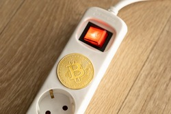 Bitcoin lying on a power supply socket. Crypto currency BTC which is mined under high power consumption due to the amount of processing. The golden coin is very expensive.