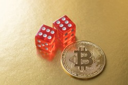 Bitcoin metal coin and two red dice with the result six and six on a golden illuminated surface