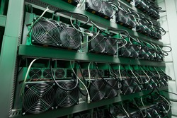Bitcoin miners in large farm. ASIC mining equipment on stand racks mine cryptocurrency in steel container. Blockchain techology application specific integrated circuit datacenter. Server room lights.