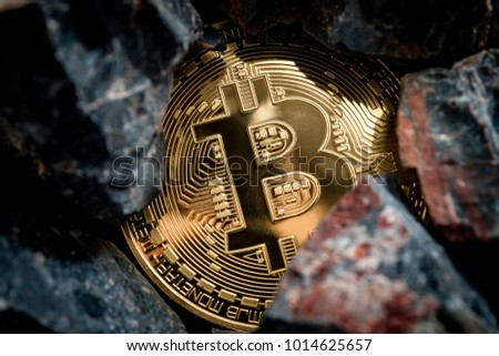 Bitcoin mining and cryptocurrency concept with a golden coin submerged in black stones compared to the traditional gold mining #1014625657